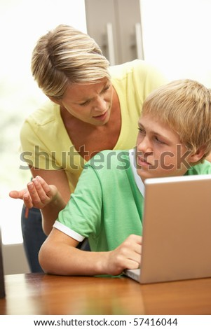 Angry Mother And Teenage Son Using Laptop At Home - stock photo