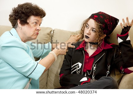 Angry mother pointing the finger at her rebellious teenage daughter.  Focus on the mom. - stock photo