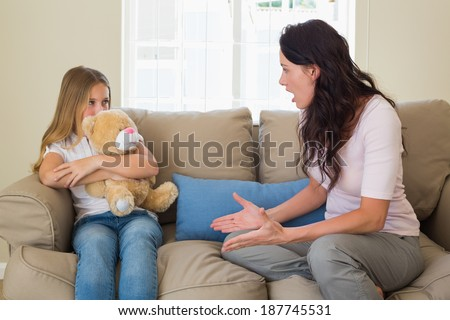Angry mother shouting at daughter while sitting on sofa at home - stock photo