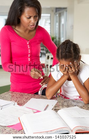 Angry Mother Telling Off Daughter About Homework - stock photo