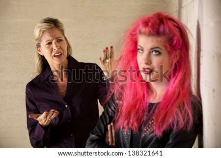Angry mother with teenage daughter in leather jacket