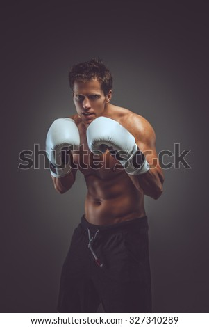 Angry muscular fighter in boxing gloves over grey background. - stock photo