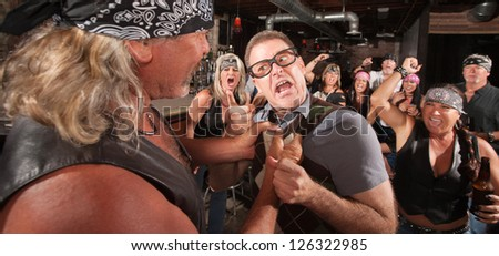 Angry nerd threatens bully gang member in bar - stock photo