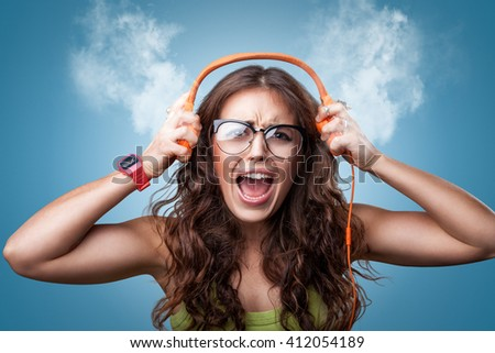 Angry nervous girl in headphones listening to music and screaming loud blowing white smoke coming out of ears. Closeup portrait girl on blue background. Negative emotion facial expression feeling - stock photo