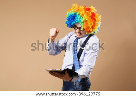 Angry office worker punches tablet. Businessman with tablet computer. Close-up Portrait of business man in clown wig using a tablet to access the internet. Business concept. Multitasking - stock photo