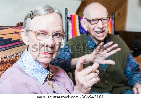 Angry old couple sitting in living room woman pointing - stock photo