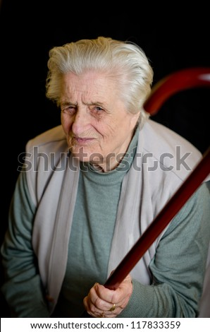 Angry old woman on black background - stock photo