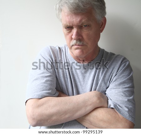 angry older man with his arms crossed - stock photo