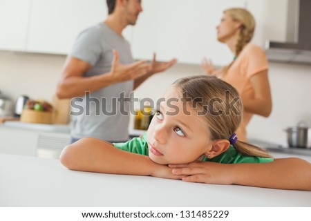 Angry parents arguing behind a sad girl at home