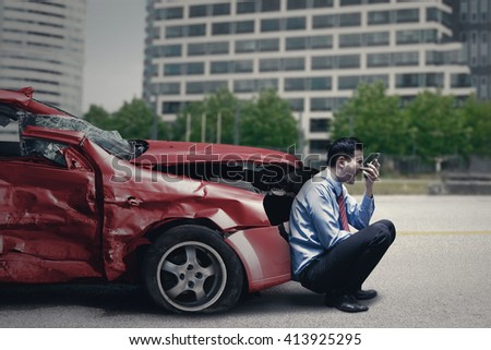 Angry person speaking on the cellphone while sitting in front of a broken car after traffic accident - stock photo