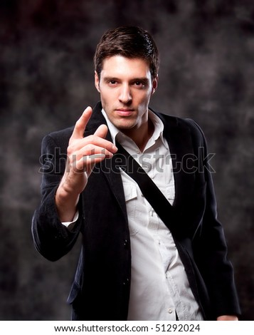 Angry Pointing Businessman isolated on dark background - stock photo
