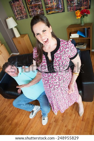 Angry pregnant woman grabbing her husband's collar - stock photo