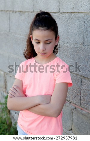 Angry preteen girl with pink t-shirt in the street - stock photo