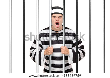 Angry prisoner standing behind bars isolated on white background