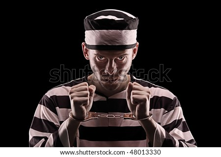 Angry prisoner with handcuffs isolated on black background - stock photo