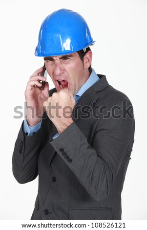 angry real estate businessman shouting on his cell phone - stock photo