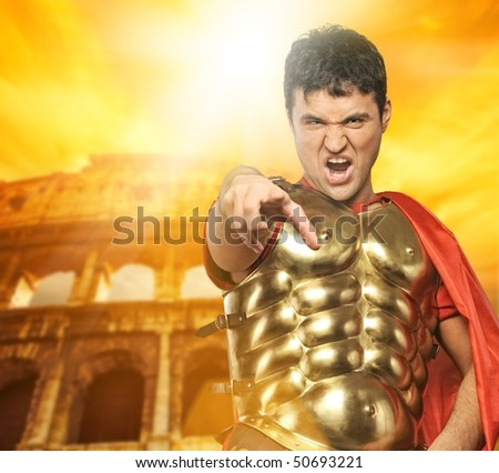 Angry roman legionary soldier in front of coliseum - stock photo