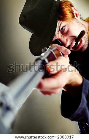 Angry rugged young man with a rifle and cowboy hat. Looks furious at something, probably going to shoot it. Smoking a cigar. - stock photo
