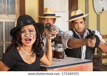 Angry 1920s vintage gangsters with weapons and whiskey - stock photo