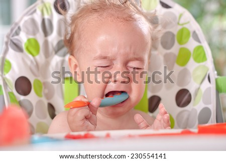 Angry sad disobedient baby child will not eat, feeding problems - stock photo