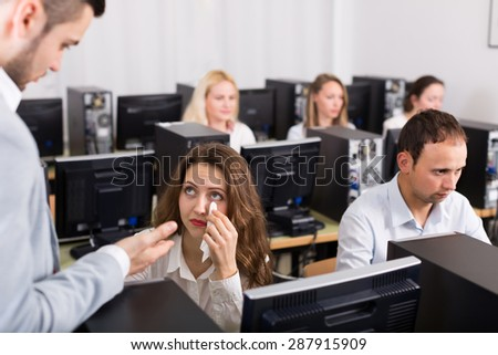 Angry sales department manager scolding crying female office worker 