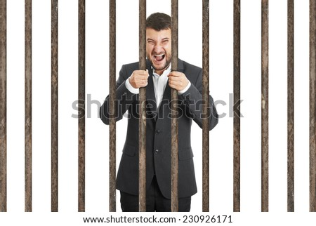angry screaming businessman behind the prison cell over white background - stock photo