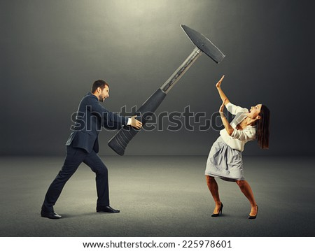 angry screaming man holding big hammer and hitting scared woman. photo in the dark room - stock photo