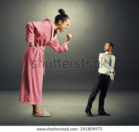 angry screaming woman shouting at small scared man. photo in the dark room - stock photo