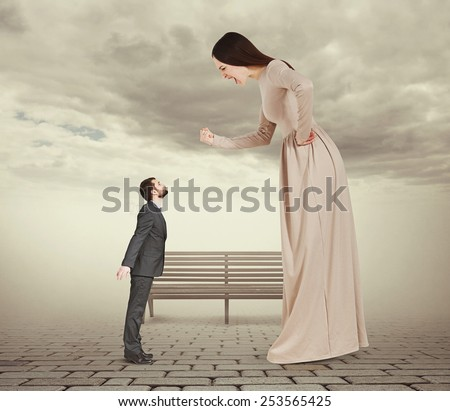 angry screaming woman showing fist and looking down at small kissing man. concept photo in foggy park - stock photo