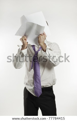 angry scruffy businessman crumpling up papers covering his face - stock photo