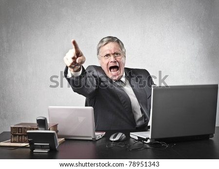 Angry senior businessman sitting at his desk and screaming - stock photo