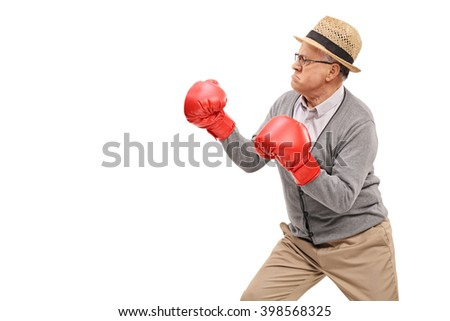Angry senior with red boxing gloves prepared for a fight isolated on white background - stock photo