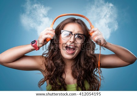 Angry shocked girl in headphones listening to music and screaming loud blowing white smoke coming out of ears. Closeup portrait girl on blue background.Negative human emotion facial expression feeling - stock photo