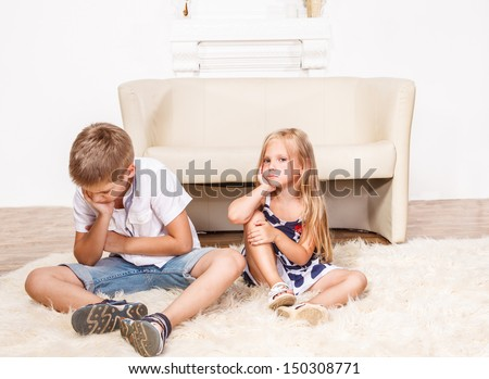 Angry siblings sitting on the carpet - stock photo