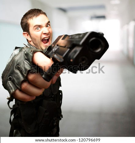 Angry Soldier Holding Gun against an abstract background - stock photo