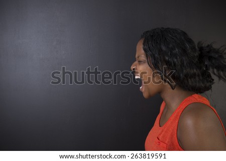 Angry South African or African American woman teacher shouting on blackboard background - stock photo