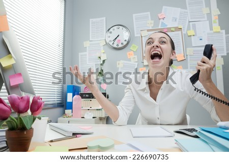 Angry stressed businesswoman in office shouting at phone. - stock photo