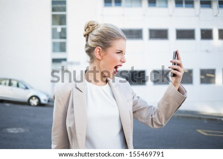 Angry stylish businesswoman shouting at her phone outdoors on urban background - stock photo
