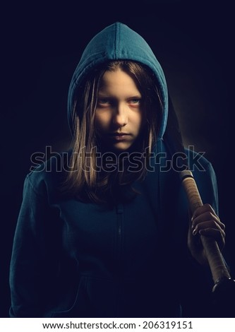 Angry teen girl in hood with baseball-bat - stock photo