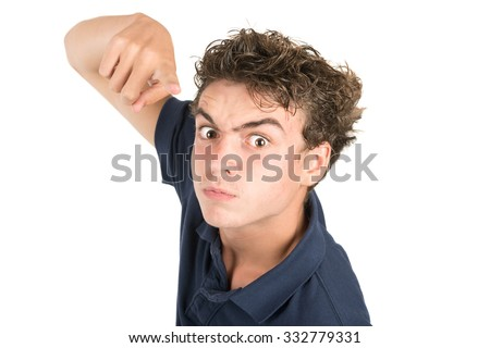Angry teenage boy making faces isolated in white