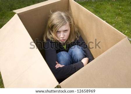 angry teenage girl sitting in a cardboard box, looking up - stock photo