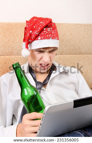 Angry Teenager in Santa Hat with Tablet Computer and Bottle of the Beer - stock photo