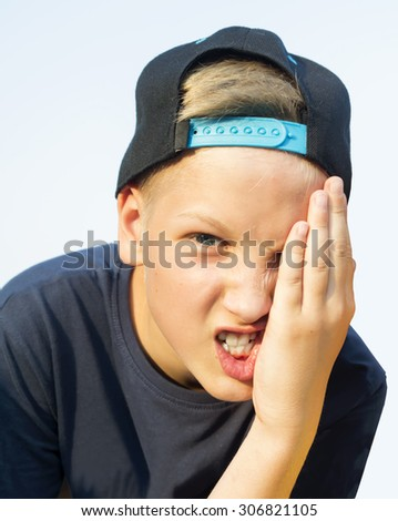 Angry teenager yell closing one eye by hand