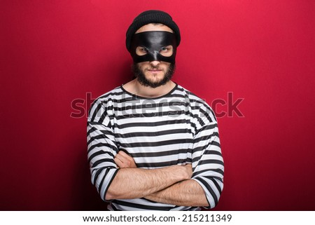 Angry thief with mask on red background    - stock photo