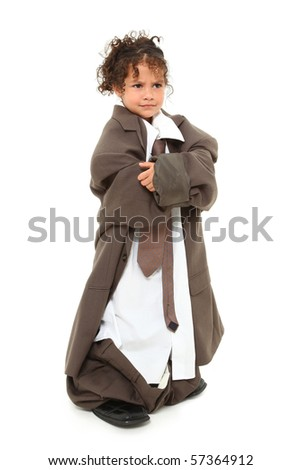 Angry three year old mixed race girl standing in baggy suit with arms crossed over white background. - stock photo