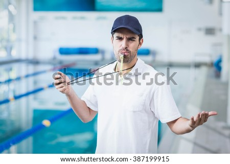 Angry trainer blowing whistle and holding stopwatch at the pool - stock photo