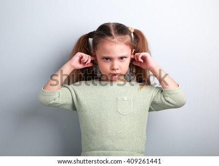 Angry unhappy kid girl covered ears the fingers and gesturing that not want to listen on blue background with empty copy space