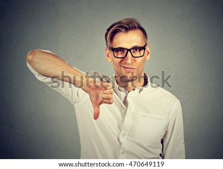 angry, unhappy, young man showing thumbs down sign, in disapproval of offer isolated on gray background. Negative human emotion facial expression feelings