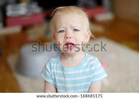 Angry upset toddler girl at home - stock photo