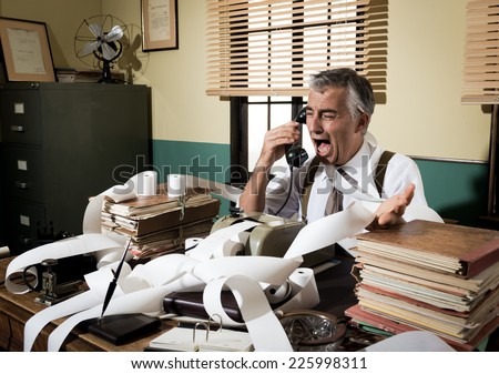 Angry vintage businessman shouting out loud at phone surrounded by adding machine tape. - stock photo